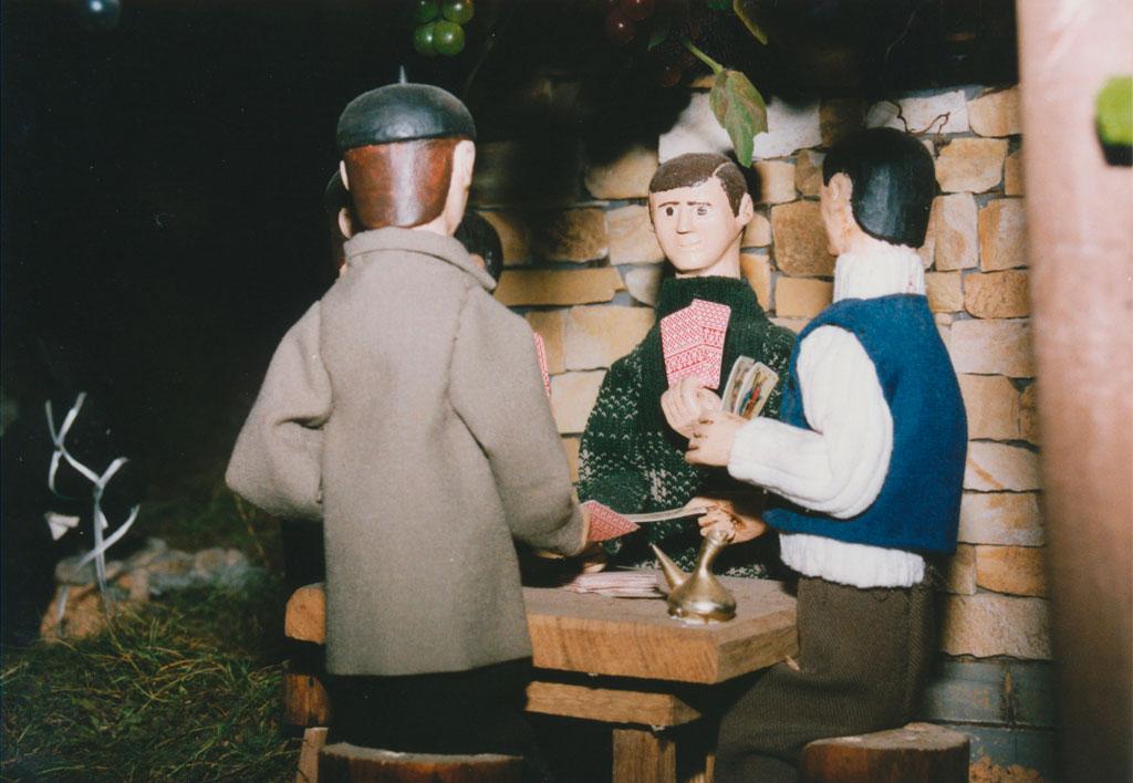 Hombres jugando a la brisca con el porrón en la mesa.