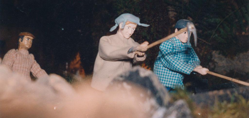 Dos labradores cavando la tierra con sus azadas.
