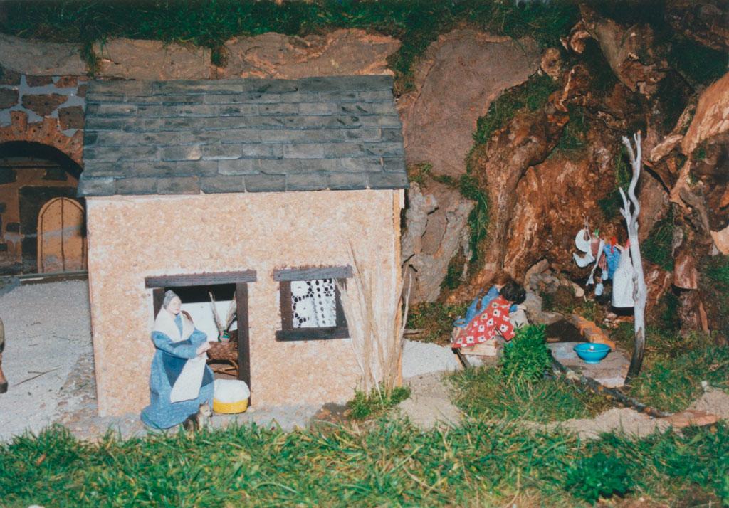 Una mujer cosiendo a la puerta de casa.