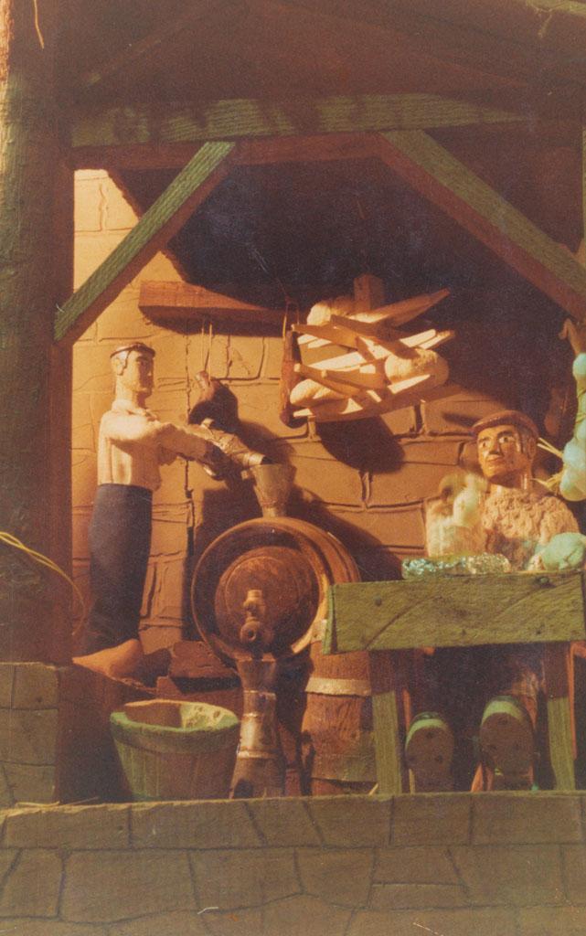 Un hombre llenado un cubeto de mosto y otro merendando en el lagar.