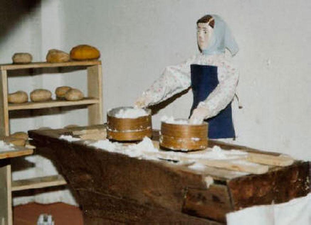 En la panadería una mujer tamizano harina.